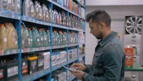 PC di With Tablet del responsabile che controlla le merci al negozio del magazzino del supermercato dell'automobile video d archivio