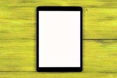 PC do tablet pc com zombaria da tela vazia acima no fundo de madeira amarelo da tabela Tabuleta na tabela de madeira tela do bran Fotos de Stock