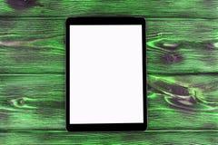 PC do tablet pc com zombaria da tela vazia acima no fundo de madeira verde da tabela Tabuleta na tabela de madeira tela do branco Fotografia de Stock