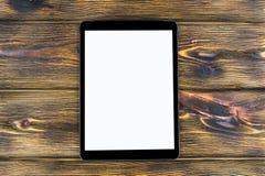 PC do tablet pc com zombaria da tela vazia isolado acima no fundo de madeira da tabela Tabuleta na tabela de madeira tela do bran Foto de Stock