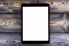 PC do tablet pc com zombaria da tela vazia isolado acima no fundo de madeira escuro da tabela Tabuleta na tabela de madeira tela  Foto de Stock Royalty Free