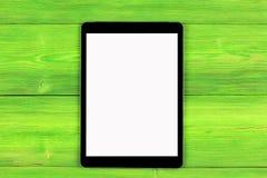 PC do tablet pc com zombaria da tela vazia isolado acima no fundo de madeira verde da tabela Tabuleta na tabela de madeira tela d Foto de Stock Royalty Free