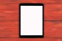 PC do tablet pc com zombaria da tela vazia isolado acima no fundo de madeira vermelho da tabela Tabuleta na tabela de madeira tel Imagem de Stock