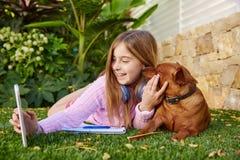 PC et chien blonds de comprimé de photo de selfie de fille d'enfant Photo stock