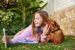 PC et chien blonds de comprimé de photo de selfie de fille d'enfant Images libres de droits