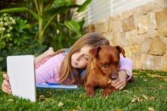 PC et chien blonds de comprimé de photo de selfie de fille d'enfant Photographie stock