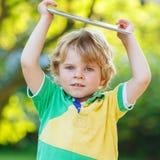 PC för minnestavla för förtjusande lycklig pojke för liten unge hållande, utomhus Royaltyfri Foto