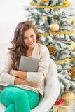PC feliz de la tableta del abarcamiento de la mujer joven cerca del árbol de navidad Imagenes de archivo