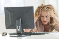 PC frustrant de Looking At Desktop de femme d'affaires dans le bureau Photographie stock