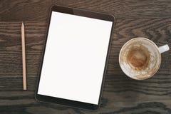 PC générique de comprimé avec l'écran vide sur la table en bois avec la tasse de café vide Photographie stock