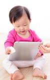 PC heureux de tablette de pièce de chéri de fille Images stock