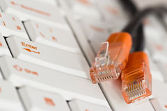 PC keyboard. With orange print and orange network cord ends Stock Photo