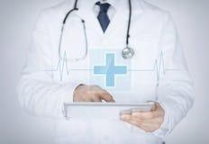 PC masculina de la tableta de la tenencia del doctor con el app médico Imagenes de archivo