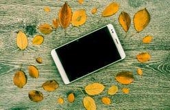 PC moderna blanca de la tableta con la pantalla vacía en blanco en el fondo de madera del vintage rústico con las hojas de otoño Fotografía de archivo libre de regalías