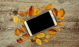 PC moderna blanca de la tableta con la pantalla vacía en blanco en el fondo de madera del vintage rústico con las hojas de otoño Imagen de archivo