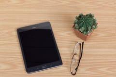 PC, monóculos e cacto pretos da tabuleta na tabela de madeira Imagem de Stock