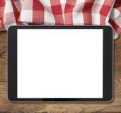 PC negra de la tableta en la tabla de madera y la comida campestre Foto de archivo