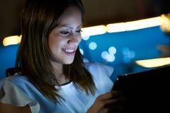 PC novo de Using Tablet do estudante interno na noite Fotografia de Stock Royalty Free