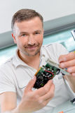 PC repair man holding graphics card Royalty Free Stock Images