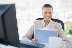 PC sofisticada sonriente de la tableta de la tenencia de la empresaria Imagenes de archivo