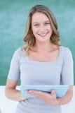 Pc sorridente della compressa della tenuta dell'insegnante davanti alla lavagna immagini stock