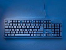 PC-Tastatur bedeckt mit dem Schnee belichtet durch blaues Neonlicht mit frohen Weihnachten der Aufschrift stockfoto