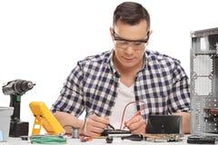 PC technician measuring electrical resistance. Male PC technician repairing a desktop computer and measuring electrical resistance isolated on white background Stock Image