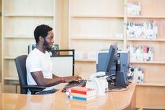 PC van bibliothecarisworking on desktop in Bibliotheek Stock Foto's
