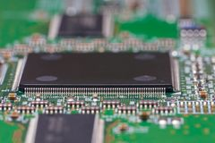 PCB with chips and SMD components. Macro photography of a fragment of a circuit Board of the electronic device. Printed circuit board with chips and SMD and QFP stock photography