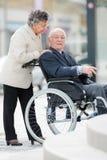 Pchać męża ` s wózek inwalidzkiego obraz stock