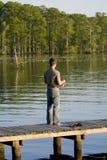 Pêche d'homme outre d'un dock Photographie stock libre de droits
