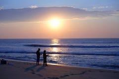 Pêche de vague déferlante de Sihoulettes au lever de soleil Images stock