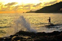 Pêcheur avec la grande vague d'éclaboussure Photo stock