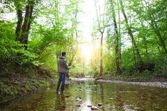 Pêcheur avec la pêche à la mouche sur la rivière de montagne Images stock