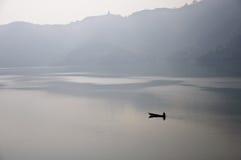 Pêcheur seul dans le bateau Photographie stock