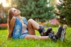 Pcteres de ruedas de la muchacha que llevan que se sientan en hierba Imagenes de archivo