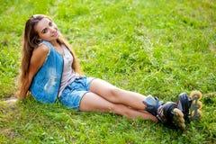 Pcteres de ruedas de la muchacha que llevan que se sientan en hierba Imagen de archivo libre de regalías