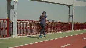 Pcteres de ruedas positivos del montar a caballo de la mujer en el puente de la ciudad metrajes