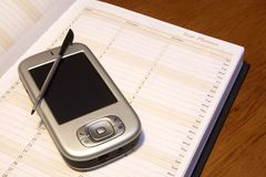 PDA and Diary. A PDA resting on a diary showing how these pocket PC's can be used to store important data Stock Photo
