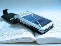 PDA em um livro Fotografia de Stock Royalty Free