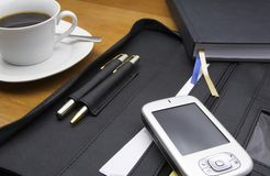 PDA in the office. Office scenario displaying a PDA pocket-PC, a file, some pens, a diary and some black coffee in a white cup royalty free stock image
