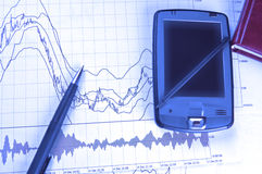 PDA and pen on stock chart. PDA and pen on Forex chart in blue lighting Stock Images