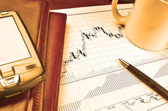 PDA on stock chart. PDA and notebooks on Forex candlestick chart in yellow lighting royalty free stock photography