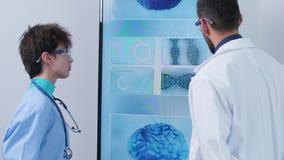 PDA tirado de enfermera y de doctor delante de la pantalla de visualización grande que analiza simulaciones del cerebro 3D metrajes