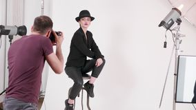 PDA tirado de modelo con un sombrero en una silla que presenta al fotógrafo almacen de metraje de vídeo