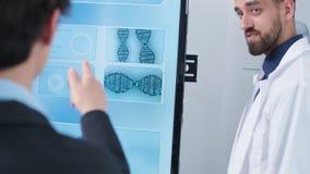 PDA tirado del científico caucásico joven que señala a una simulación del cerebro 3D almacen de video