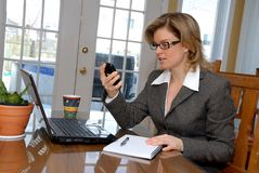 PDA woman. Woman holding a PDA with her laptop Stock Images