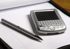 PDA y pluma en el cuaderno Imagen de archivo libre de regalías
