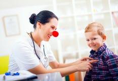 Pédiatre avec le nez de clown et patient heureux d'enfant Photos stock