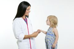 Pädiatrischer Doktor des Brunette mit blondem kleinem Mädchen Stockbild